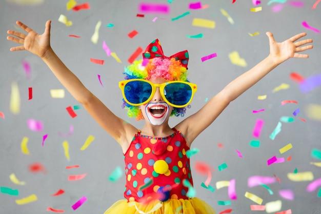 Grappige jongen clown met pper confetti. gelukkig kind thuis spelen. 1 april fool's day-concept