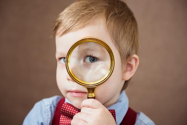 Grappige jongen die door vergrootglas met verrassing kijkt. detailopname