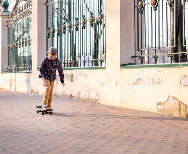 Grappige jongen die in grijze hoed op zwart skateboard in het warme groene park in het centrum van grote stad leert te schaatsen.