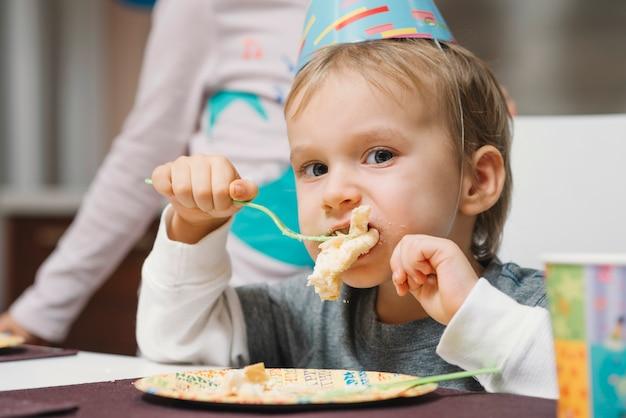 Grappige jongen die van verjaardagscake geniet