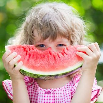 Grappige jongen die watermeloen buiten eet in het zomerpark