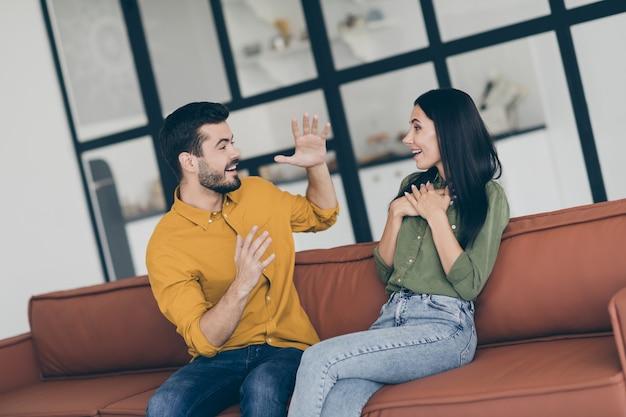 Grappige jongen en dame plezier zittend op de bank in moderne flat