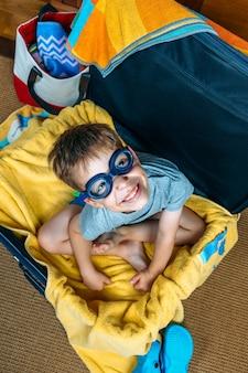 Grappige jongen glimlachend zittend in een koffer klaar om op vakantie te gaan