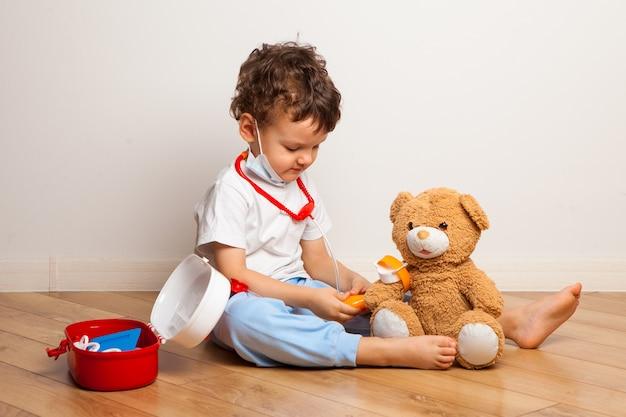 Grappige jongen in een medisch masker speelt met een teddybeer bij de dokter. een kind in een masker meet de druk en luistert met een stethoscoop naar speelgoed. virusbeschermingstraining.