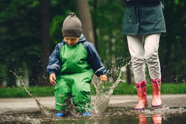 Grappige jongen in regenlaarzen spelen in een regenpark