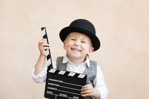 Grappige jongen klepel bord te houden. gelukkig kind plezier thuis. retro bioscoopconcept