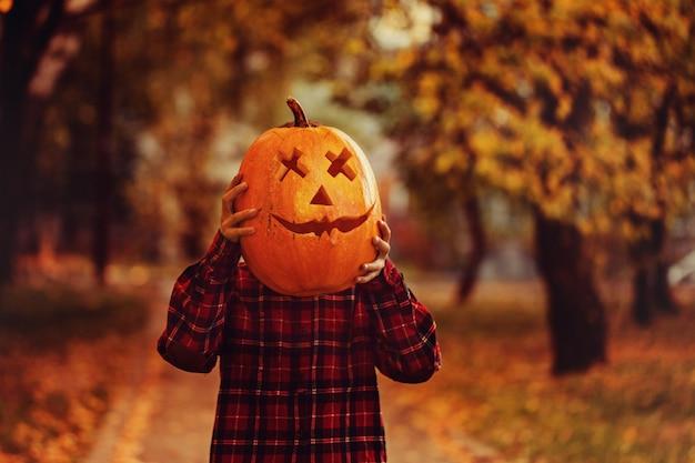 Grappige jongen met pompoen op halloween. het kind met pompoen in plaats van hoofd voor vakantie halloween in de buitenlucht.