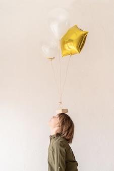Grappige jongen speelt met helium ballonnen, houdt ze op zijn hoofd