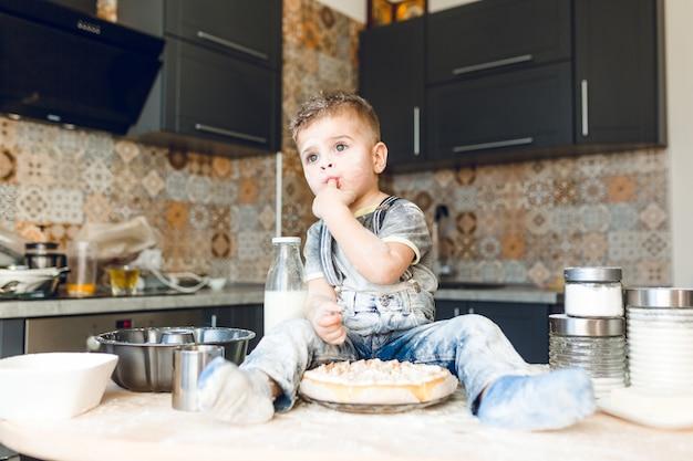 Grappige jongen zittend op de keukentafel in een akoestische keuken spelen met bloem en een taart proeven.