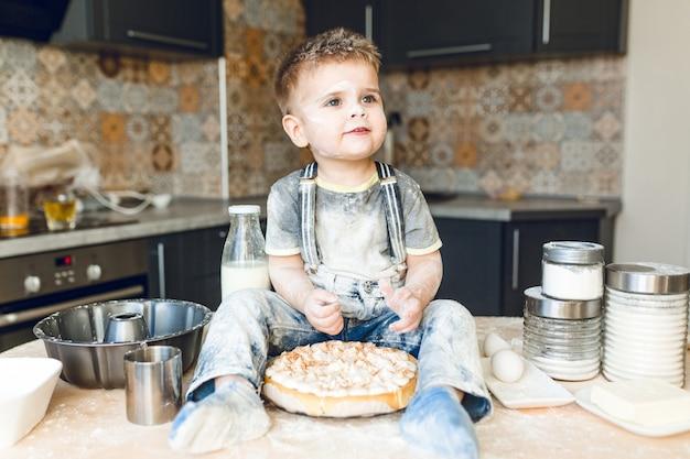 Grappige jongen zittend op de keukentafel in een akoestische keuken spelen met bloem.