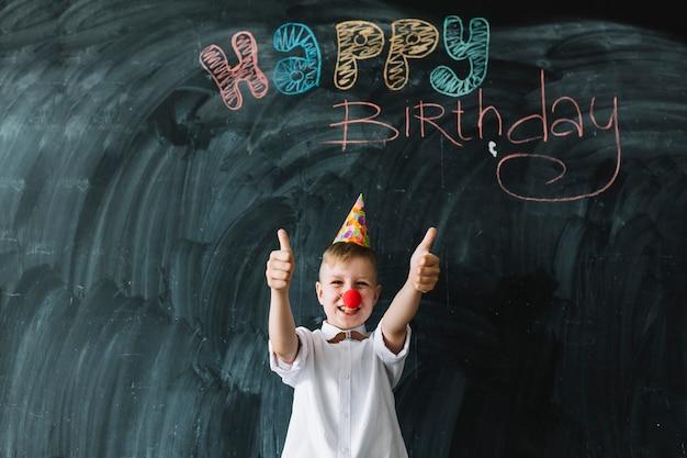 Grappige jongens gesturing duim-ups op verjaardagspartij