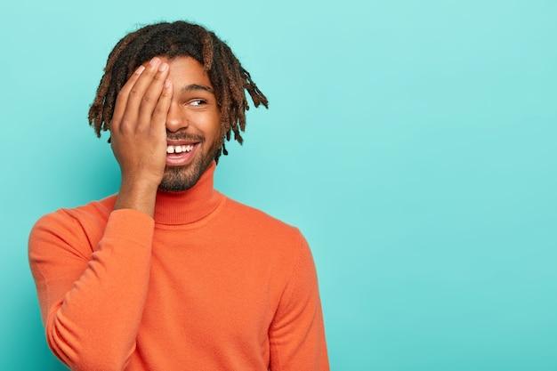 Grappige jongere met donkere huid, bedekt de helft van het gezicht met de handpalm, giechelt positief, heeft een aangename glimlach, draagt een oranje coltrui