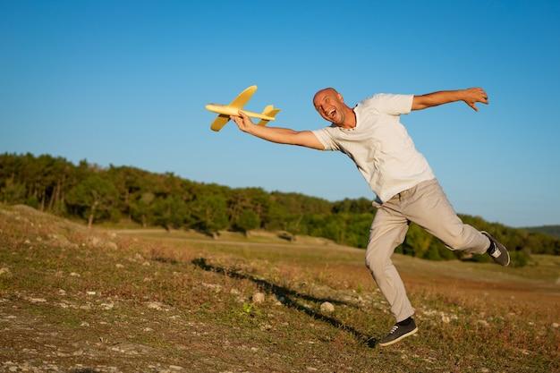 Grappige kale man met een vliegtuig in zijn hand tegen de hemel