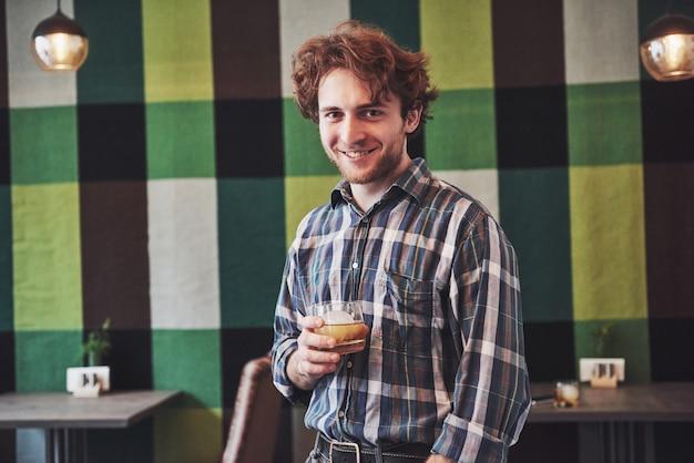 Grappige kerel die een glas whisky houdt en tegen uitstekend behang stelt