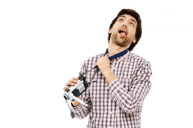 Grappige kerel die het wurgen met camerariem imiteert