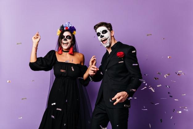 Grappige kerel en donkerharige dame met geschilderde gezichten en bloemenkroon poseren, dansen in zwarte outfit voor feest.