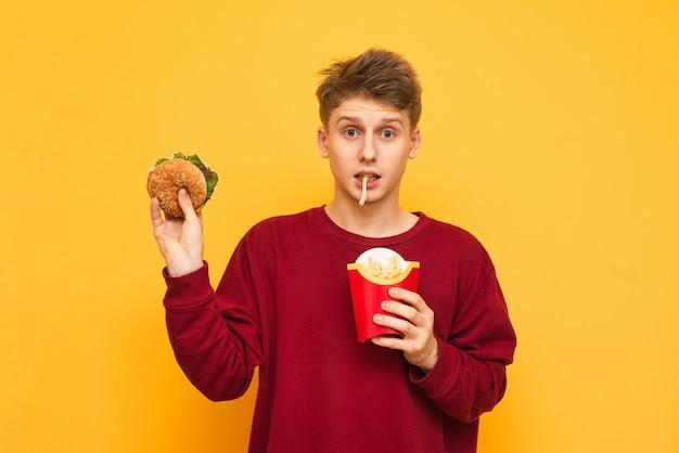 Grappige kerel houdt een hamburger in zijn handen en bijt frietjes, een student eet fastfood op een geel