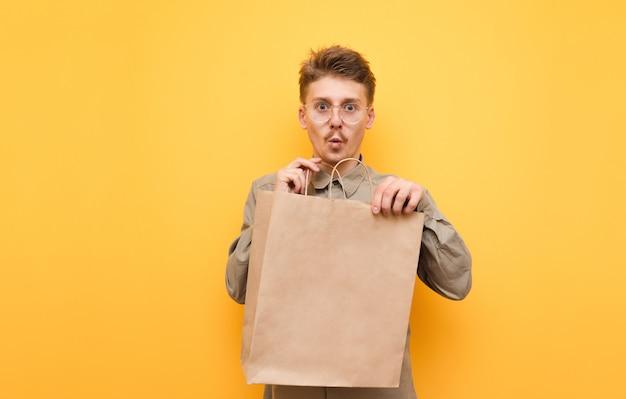 Grappige kerel in glazen met een papieren zak in zijn handen staat op een geel en met een verbaasd gezicht kijkt in de camera
