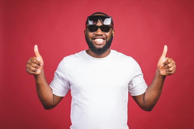 Grappige kerel in wit t-shirt en zon glases springen en kijken naar de camera. studioportret van het emotionele afrikaanse mannelijke model stellen op rode achtergrond. duimen omhoog.