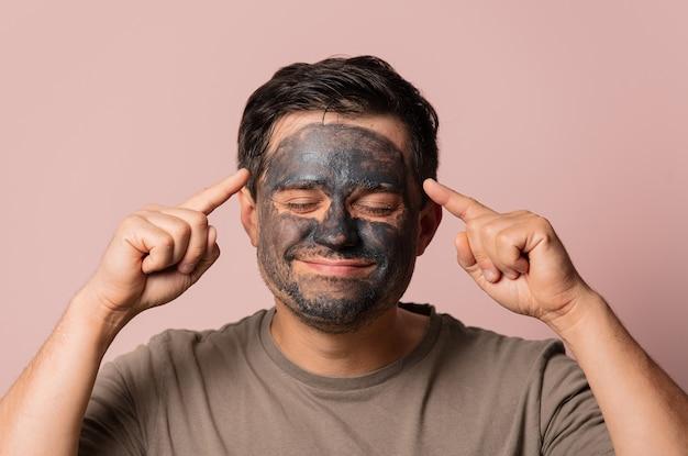Grappige kerel met een cosmetisch masker op zijn gezicht op roze