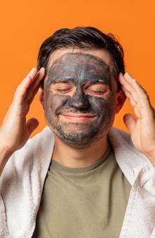 Grappige kerel met een kosmetisch masker op zijn gezicht en handdoek op sinaasappel