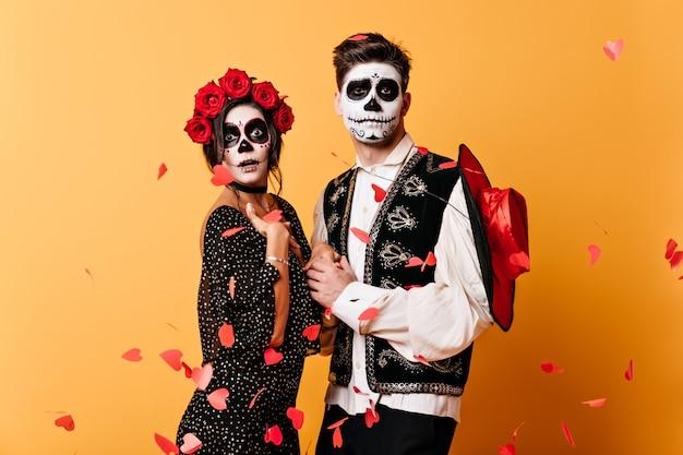 Grappige kerel met skeletmasker op zijn gezicht in mexicaans traditioneel vest houdt zijn geliefde handen vast, poseren onder confetti van papieren harten