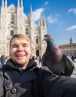 Grappige kerel selfie met duif voor kathedraal duomo