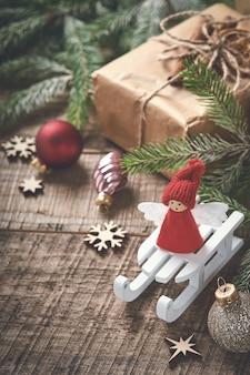 Grappige kerst engel fir boomtakken en geschenkdozen op winter besneeuwde achtergrond met besneeuwde takken. kerst of winter concept.