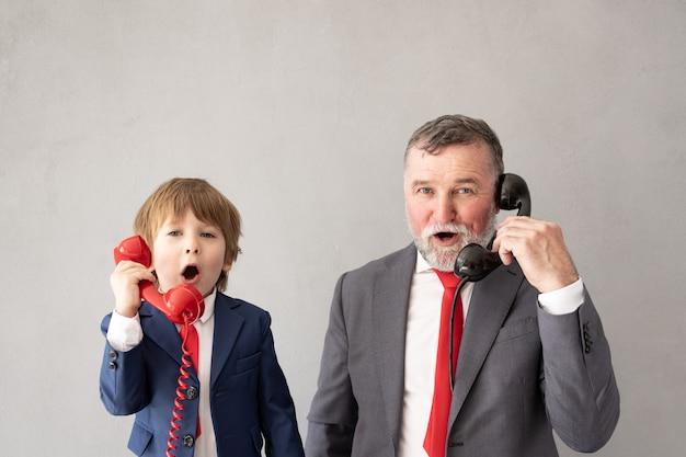 Grappige kind en senior man doen alsof ze zakenlieden zijn. grootvader en kind spelen thuis. onderwijs, opstarten en bedrijfsideeconcept