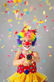 Grappige kinderclown met feestknoppen. gelukkig kind thuis spelen. 1 april fool's day-concept