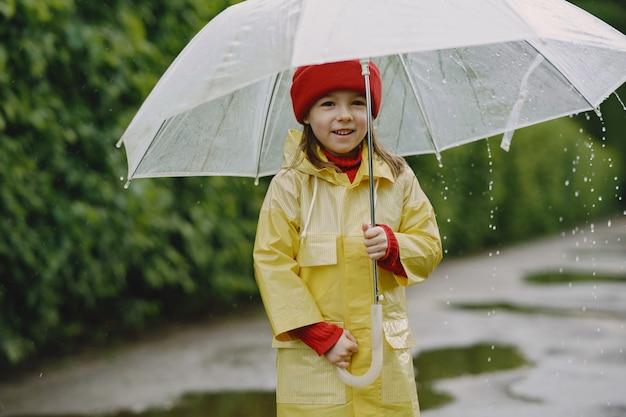 Grappige kinderen in regenlaarzen spelen door een plas