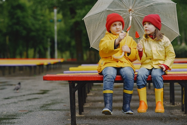 Grappige kinderen in regenlaarzen spelen in een regenachtig park