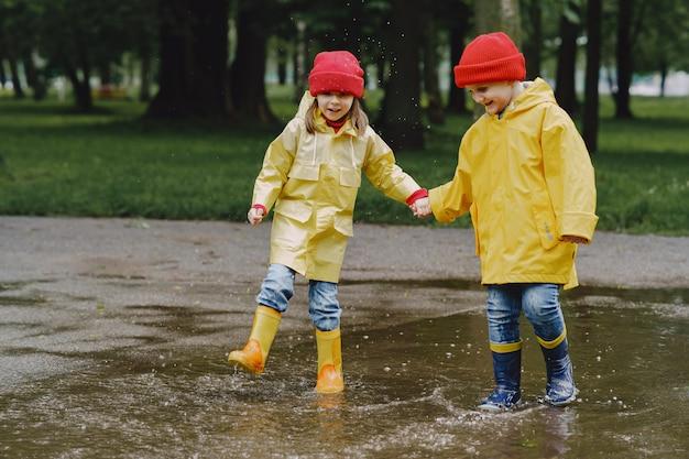 Grappige kinderen in regenlaarzen spelen met papieren schip door een plas