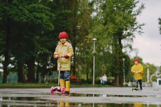 Grappige kinderen in regenlaarzen spelen met schaatsen