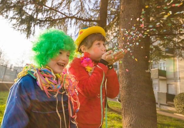 Grappige kinderen meisjes vieren carnaval glimlachend en plezier maken met kleurrijke confetti