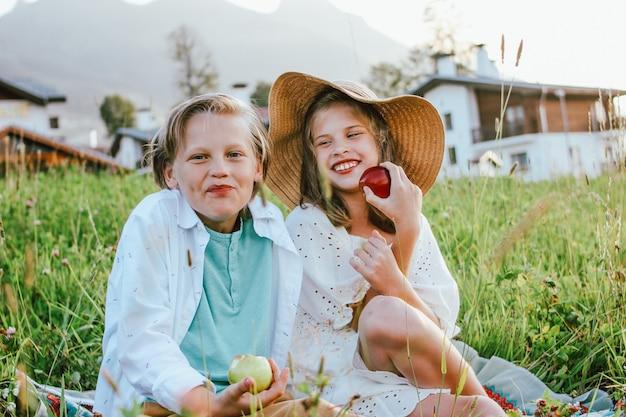 Grappige kinderen met appels broer en zus vrienden zitten in gras op de achtergrond van het dorp, landelijke scène