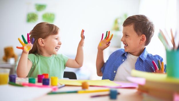 Grappige kinderen tonen hun handpalmen de geschilderde verf.