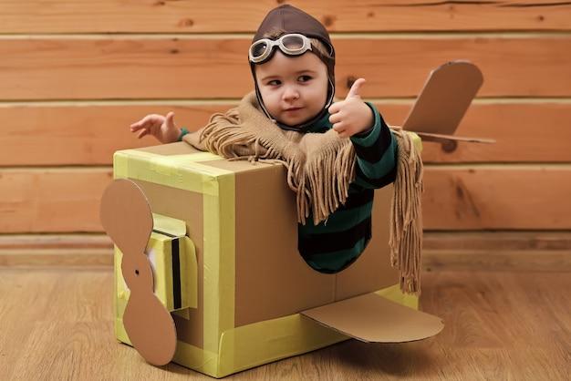 Grappige kindpiloot die een kartondoos vliegt. kind droom. vliegtuigbouw, onderwijs. duimen omhoog.