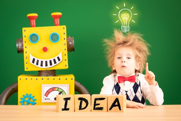 Grappige kindstudent met stuk speelgoed robot tegen groen bord.