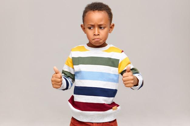 Grappige kleine afro-amerikaanse jongen in gestreepte trui poseren duimen opgevend, goed gedaan zeggen, iemand prijzen voor goed uitstekend werk, succes bij studie of werk. zwart kind goedkeuren