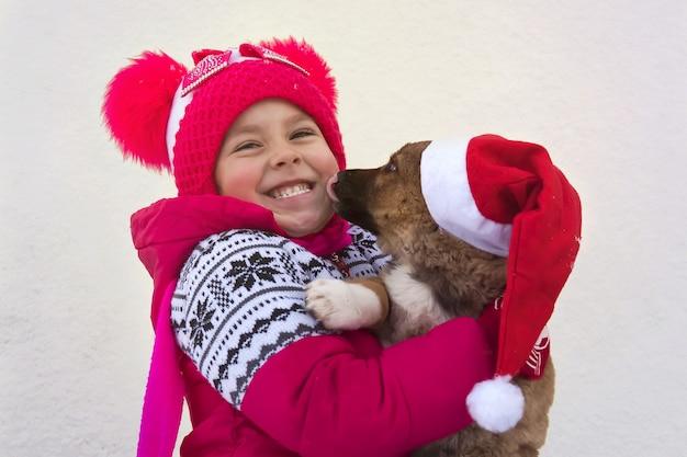 Grappige kleine baby in santa claus en hond teckel. puppy duitse herder likken tong lachend gezicht van het kind. pet van de kerstman op de hond. een symbool van kerstmis en het nieuwe 2018