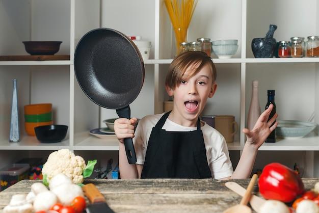 Grappige kleine chef-kok met een pan in de keuken. jongen die chef-kokschort draagt. kid droomt van toekomstig beroep.