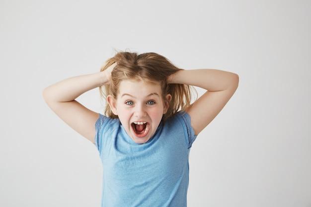 Grappige kleine dame met felblauwe ogen in blauw t-shirt schreeuwend en super opgewonden over nieuwe speelgoedpop die vader voor verjaardag kocht.