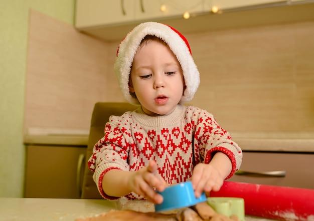 Grappige kleine jongen die kerstkoekjes kookt, helper van de kerstman