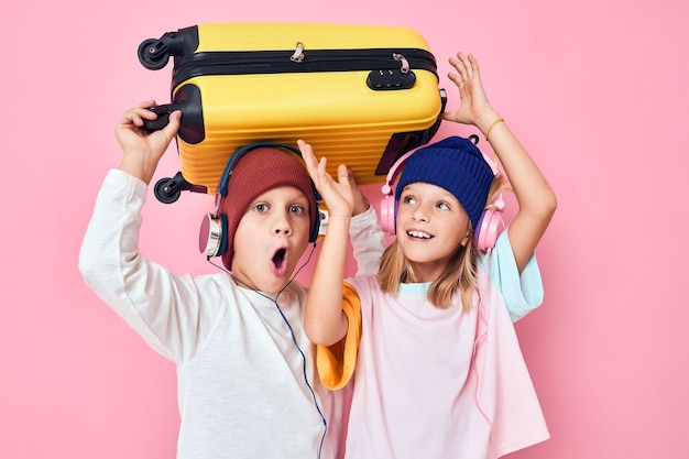 Grappige kleine jongen en meisje gele koffer met koptelefoon studio poseren