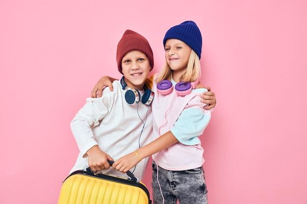 Grappige kleine jongen en meisje stijlvolle kleding koffer hoofdtelefoon roze kleur achtergrond