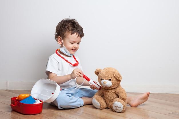 Grappige kleine jongen in een medisch masker, een peuter in het pak van een arts met een stethoscoop maakt een injectie in een teddybeer. spel in het beroep. vaccinatie. kinderen leren medische procedures