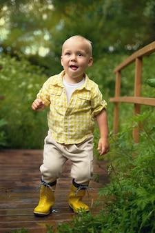 Grappige kleine jongen in gele rubberen laarzen staat op de brug