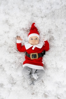 Grappige kleine jongen in santa kostuum is klaar om kerstmis en nieuwjaar te vieren. kerstkaart