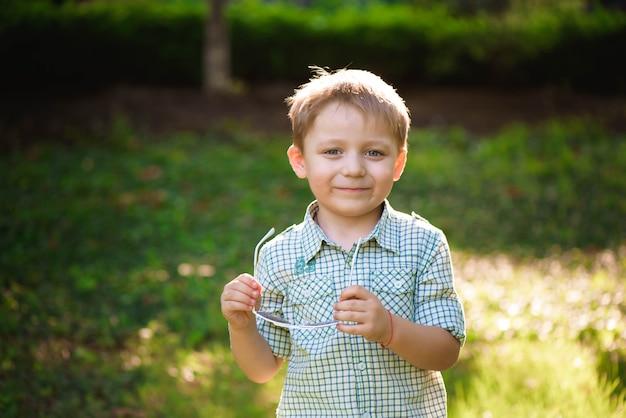 Grappige kleine jongen in zonnebril. kind jongen in zonnebril in de camera kijken op zomerdag achtergrond
